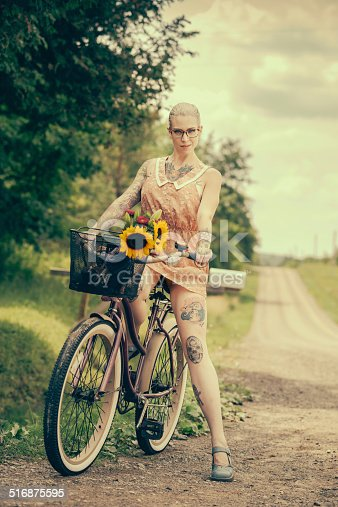 Young blonde woman (with tattoos on her arms and legs) posing on a deserted country road with her vintage cruiser style bicycle.
