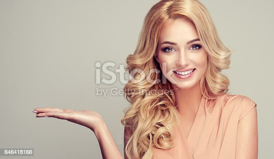 Attractive blonde woman with wide smile and points to the side and presents your product.