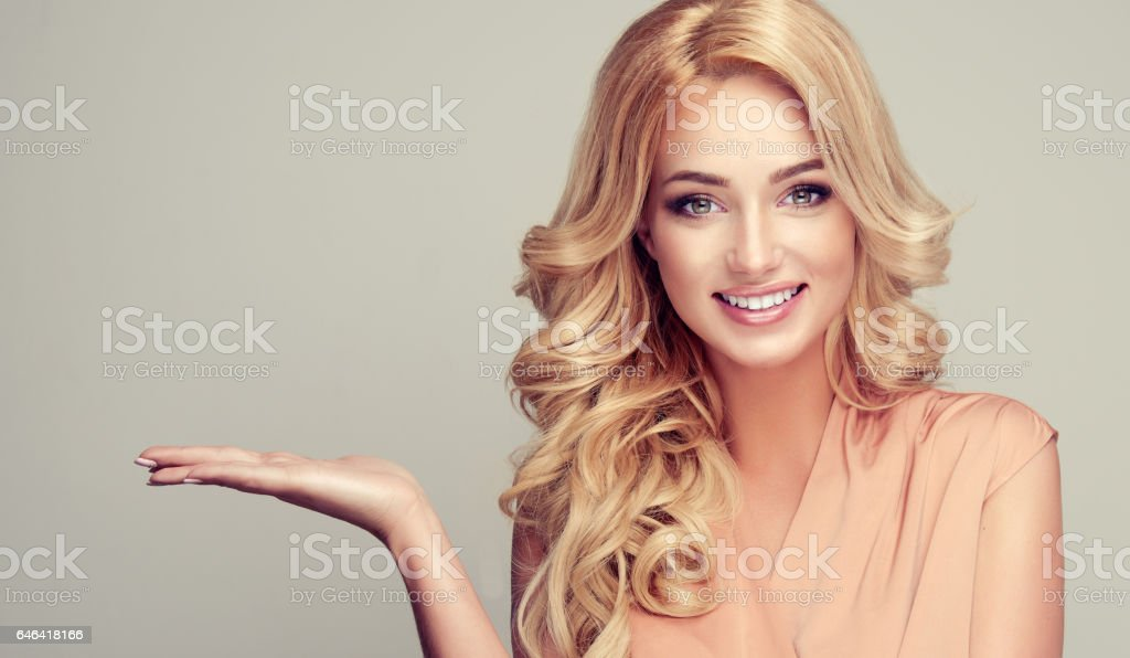 Blonde woman with curly hair demonstrates your product. – zdjęcie
