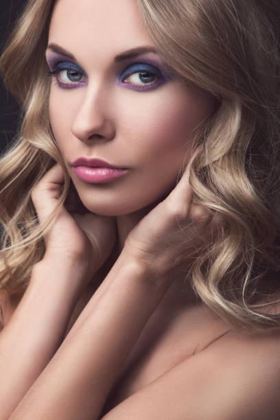 blonde frau mit lockigem haar - lila augen make up stock-fotos und bilder