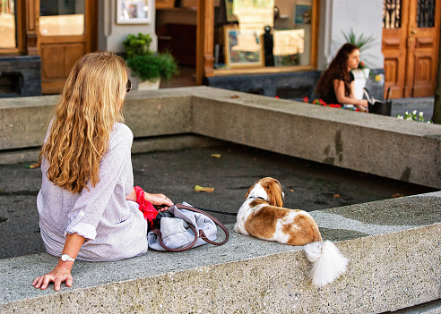 Blonde woman with dog relaxing in shade in Montreux Swiss