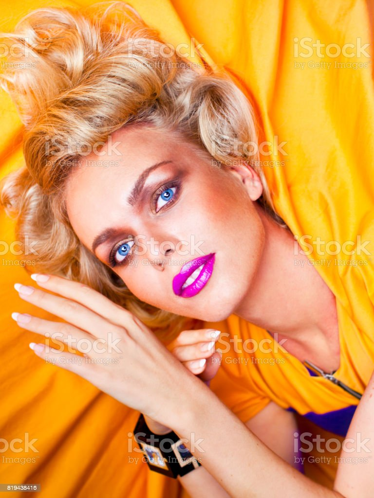 Blonde woman with fuchsia lipstick and trendy hairstyle dressed in couture blue bodysuit with yellow cape and fancy bracelet at the photo studio posing for beauty portrait stock photo