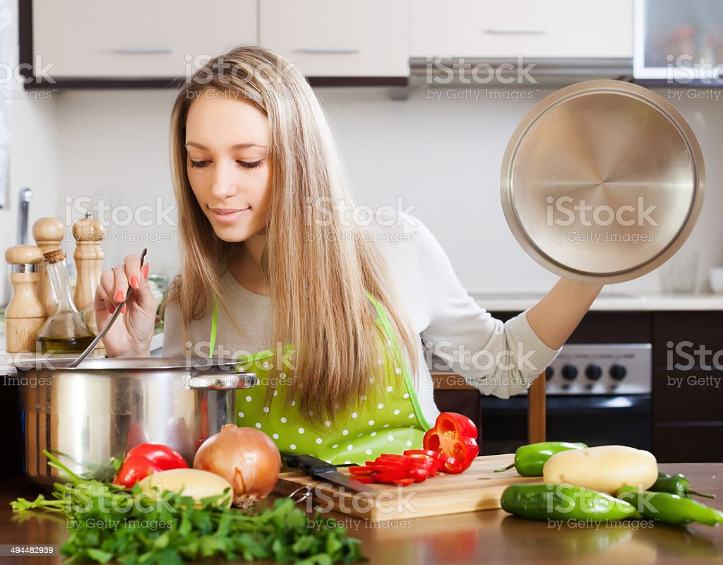 blonde woman with ladle testing soup from pan stock photo
