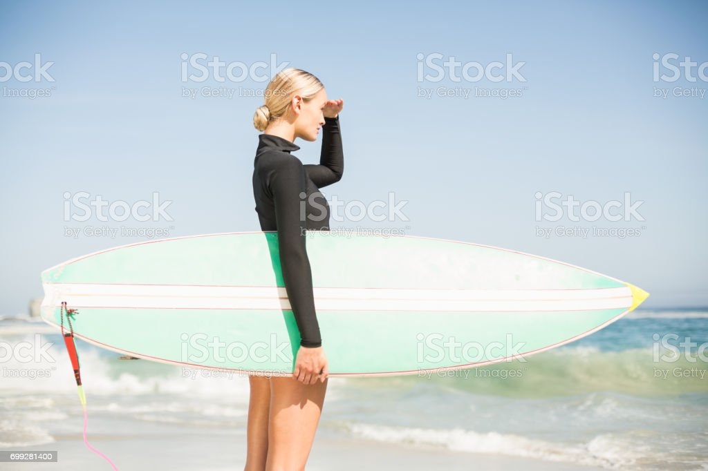 Blonde woman with surfboard shielding eyes at beach stock photo