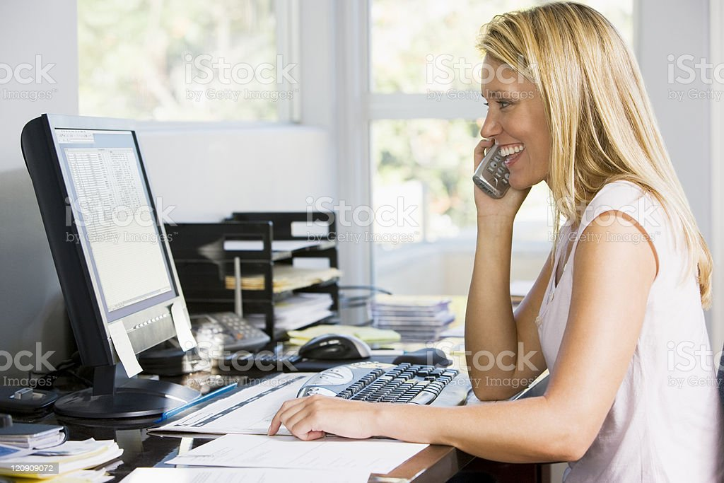 Blonde woman with telephone in front of computer royalty-free stock photo