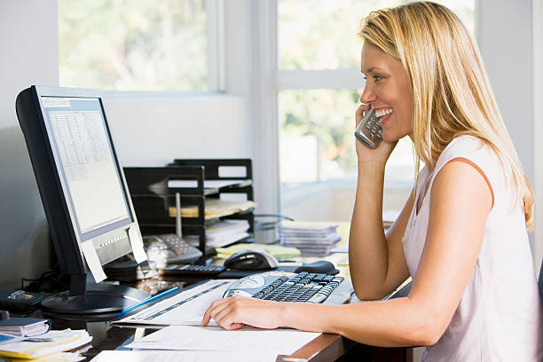 Blonde woman with telephone in front of computer Woman in home office using computer talking on telephone smiling cordless phone stock pictures, royalty-free photos & images