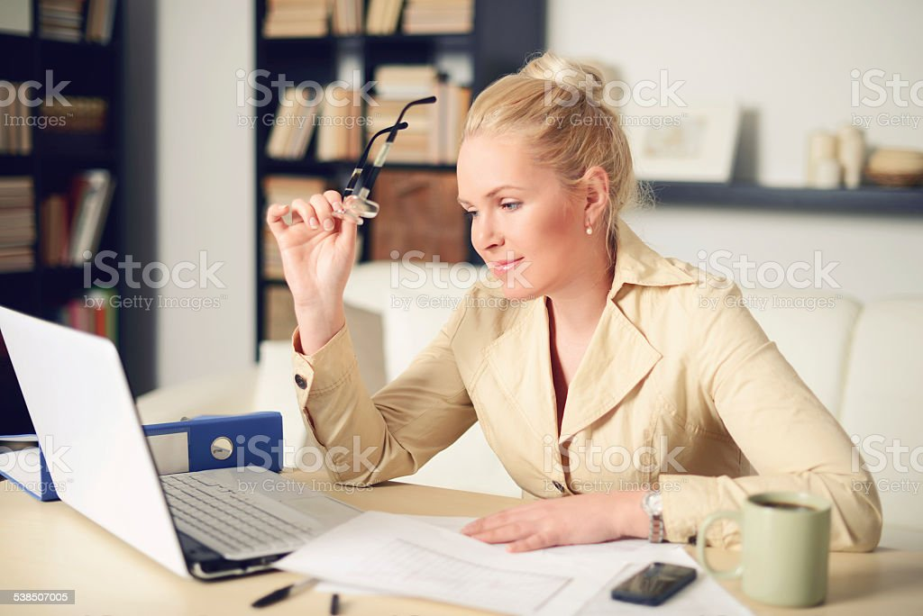blonde woman working at home stock photo