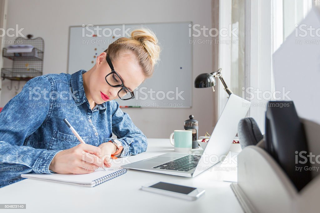 Blonde woman working in a home office Blonde woman wearing jeans shirt and nerd glasses sitting at the desk in a home office and taking notes, laptop on the desk. Adult Stock Photo