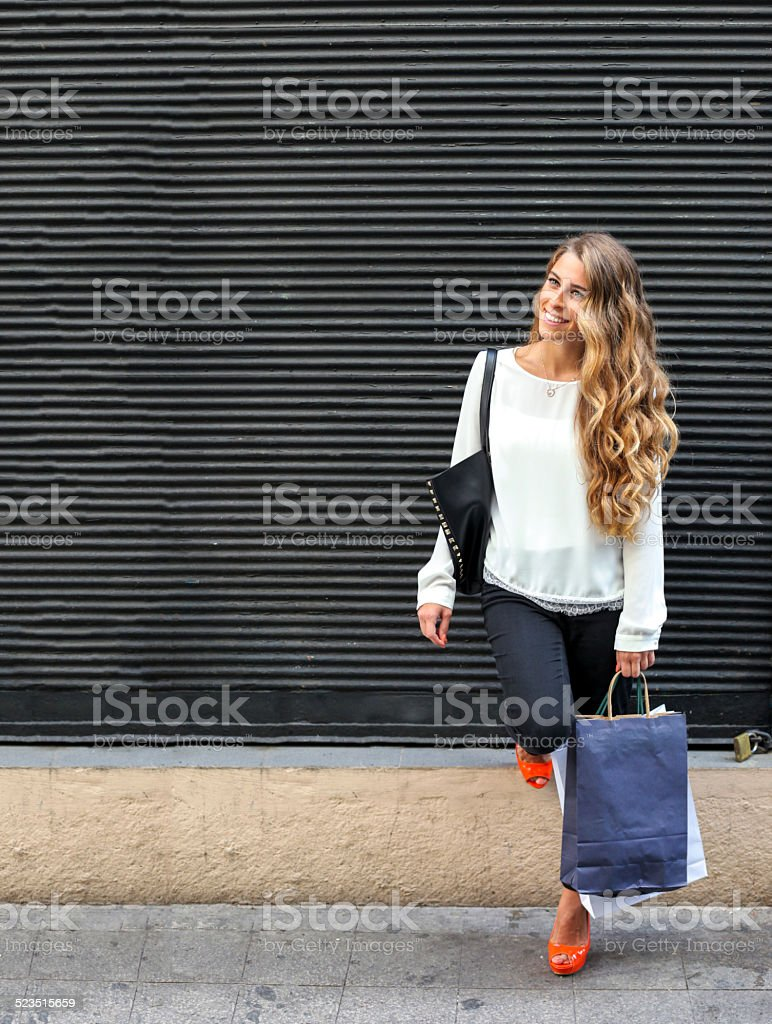 Blonde young girl holding shopping packet stock photo
