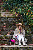 Blonde young girl in straw hat is sitting on stone stairs with her dog in Autumn.