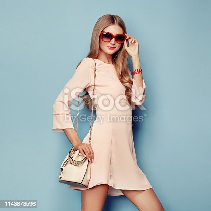 Portrait of Fashion Young woman in Pink Dress. Lady in Stylish Coral Summer Outfit. Girl Posing on a Blue Background. Stylish Hairstyle. Model Posing with Summer Handbag and Sunglasses