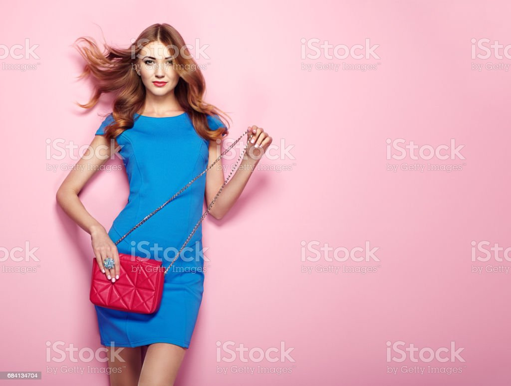Blonde young woman in elegant blue dress stock photo