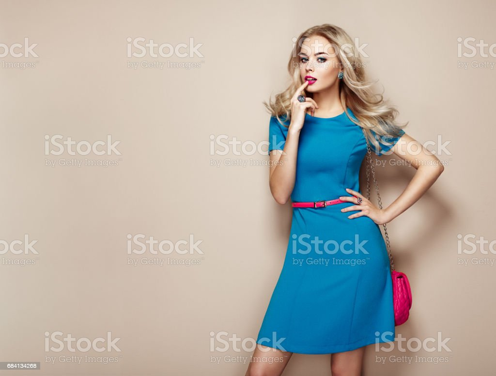 Blonde young woman in elegant blue summer dress stock photo