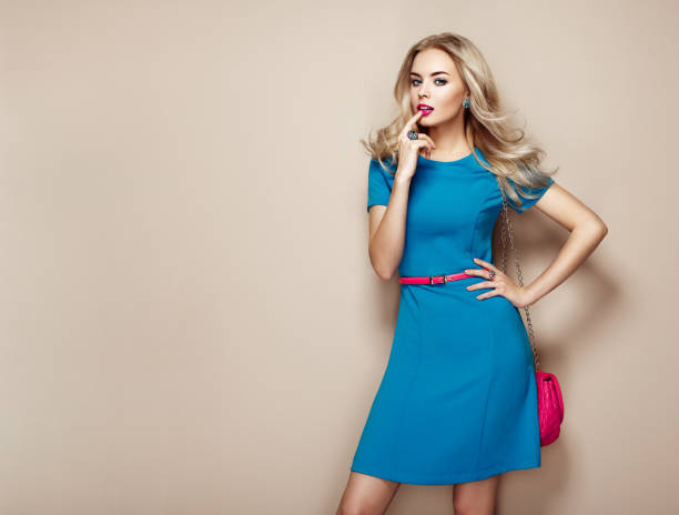 Blonde young woman in elegant blue summer dress Blonde young woman in elegant blue summer dress. Girl posing on a beige background. Jewelry and hairstyle. Girl with handbag. Fashion photo dress stock pictures, royalty-free photos & images