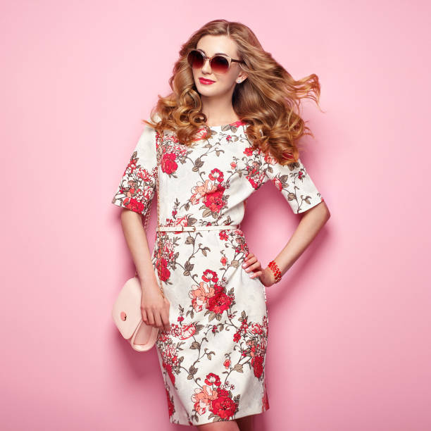 Blonde young woman in floral spring summer dress Blonde young woman in floral spring summer dress. Girl posing on a pink background. Summer floral outfit. Stylish wavy hairstyle. Fashion photo. Glamour lady in sunglasses with handbag dress stock pictures, royalty-free photos & images