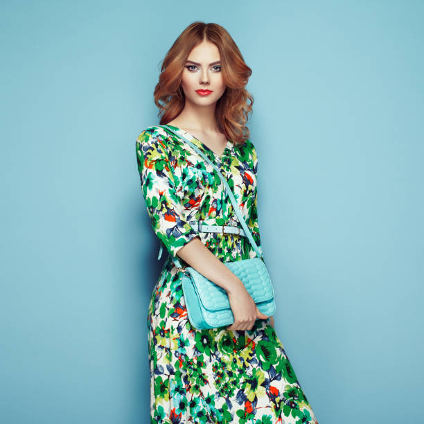 Blonde young woman in floral spring summer dress Blonde young woman in floral spring summer dress. Girl posing on a pink background. Summer floral outfit. Stylish wavy hairstyle. Fashion photo. Glamour lady with handbag dress stock pictures, royalty-free photos & images
