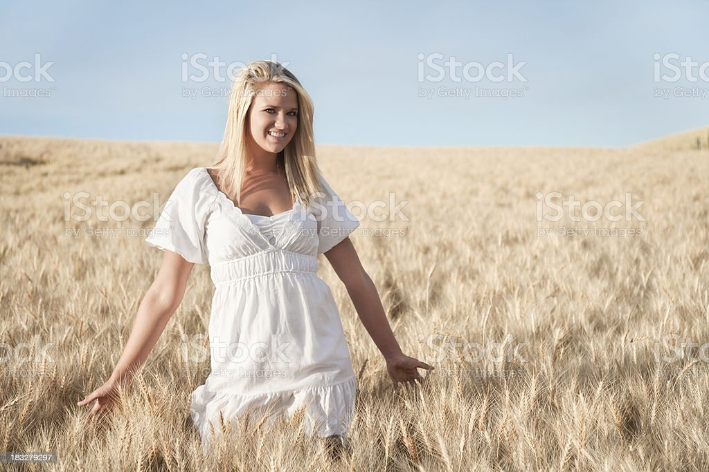 Blonde Young Woman in Golden Wheat Field Photo of an attractive young blonde woman standing in a wheat field on a warm summer day. 18-19 Years Stock Photo