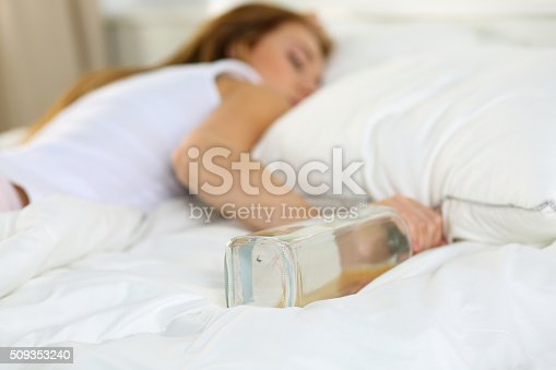 istock Blonde young woman lying in bed deadly drunken 509353240