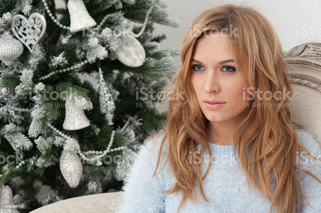 Blonde young woman sit in chair near Christmas tree stock photo