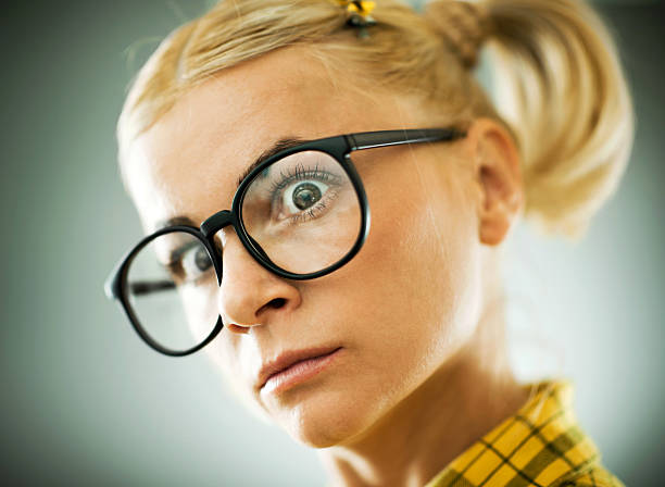 blonde young woman with a cross expression on her face. - stupidblonde stock pictures, royalty-free photos & images