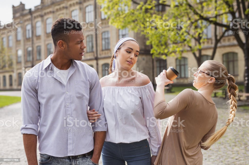 Blonde-haired inattentive student spilling coffee on bypasser royalty-free stock photo