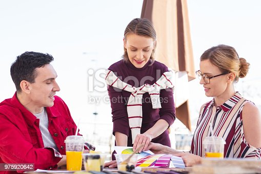 istock Blonde-haired woman wearing burgundy shirt staying near friends 975920642