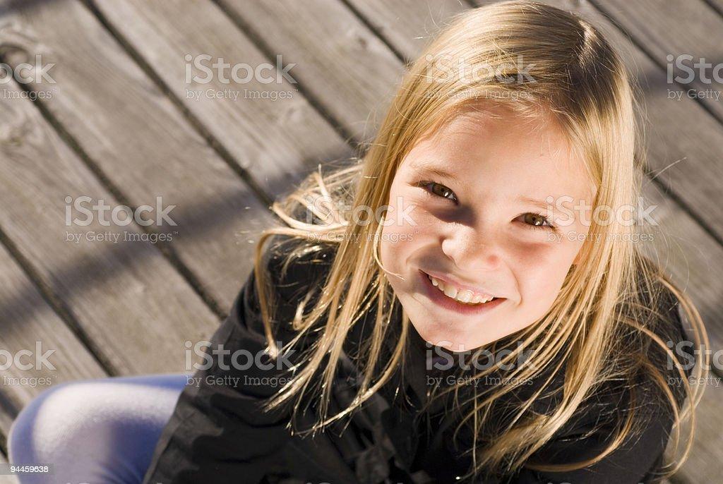 blondes Mädchen sitzt auf Holzboden royalty-free stock photo