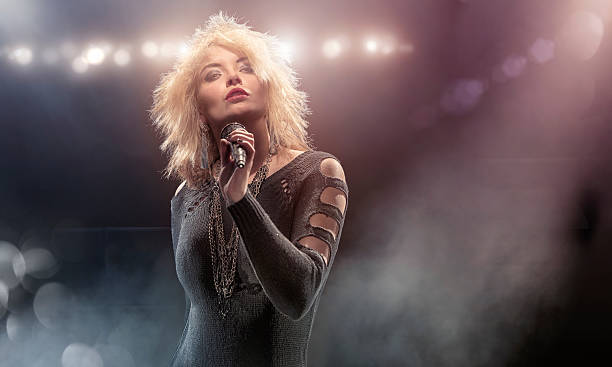 Blondie Lookalike Singer on Stage Portrait of a blond female singer dressed in alternative fashion with a black punk / grunge top and chains holding up a microphone during a stage performance in a floodlit indoor music venue with spotlights and smoke. The singer is a Blondie lookalike. With intentional lens flare and bokeh.  pop musician stock pictures, royalty-free photos & images