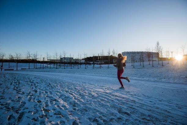 blondie frau läuft bei winter sonnenuntergang. - gewicht schnell verlieren stock-fotos und bilder