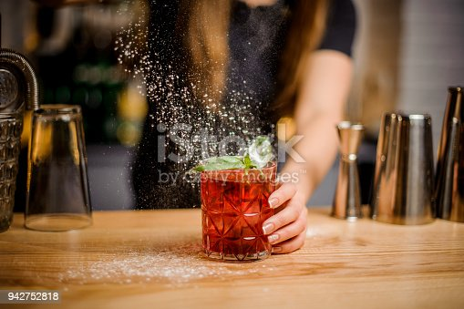 istock blondy barmaid finishes preparation of cocktail by adding a bitter of powdered sugar 942752818