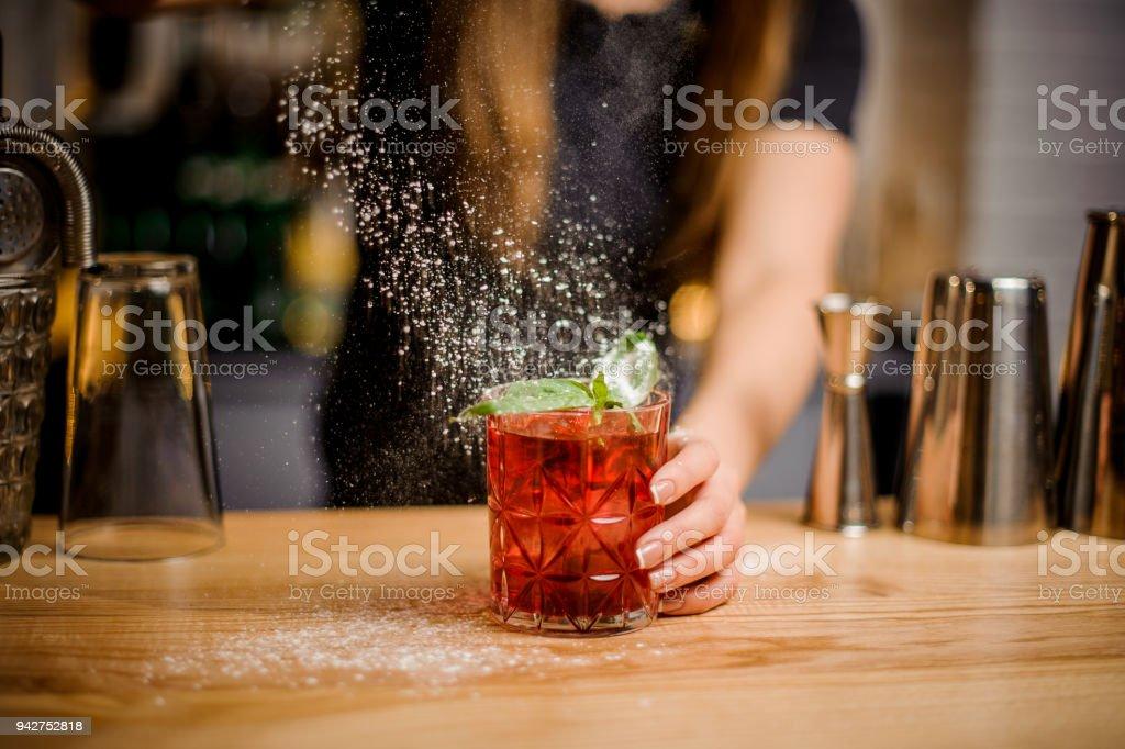 Blondy Bardame beendet Vorbereitung der cocktail durch Hinzufügen von einen bitteren Puderzucker – Foto