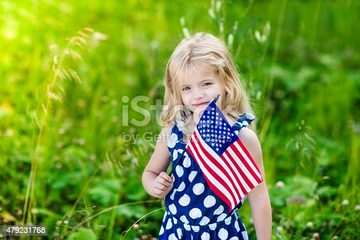 514069232 istock photo Blong smiling little girl with curly hair holding american flag 479231768