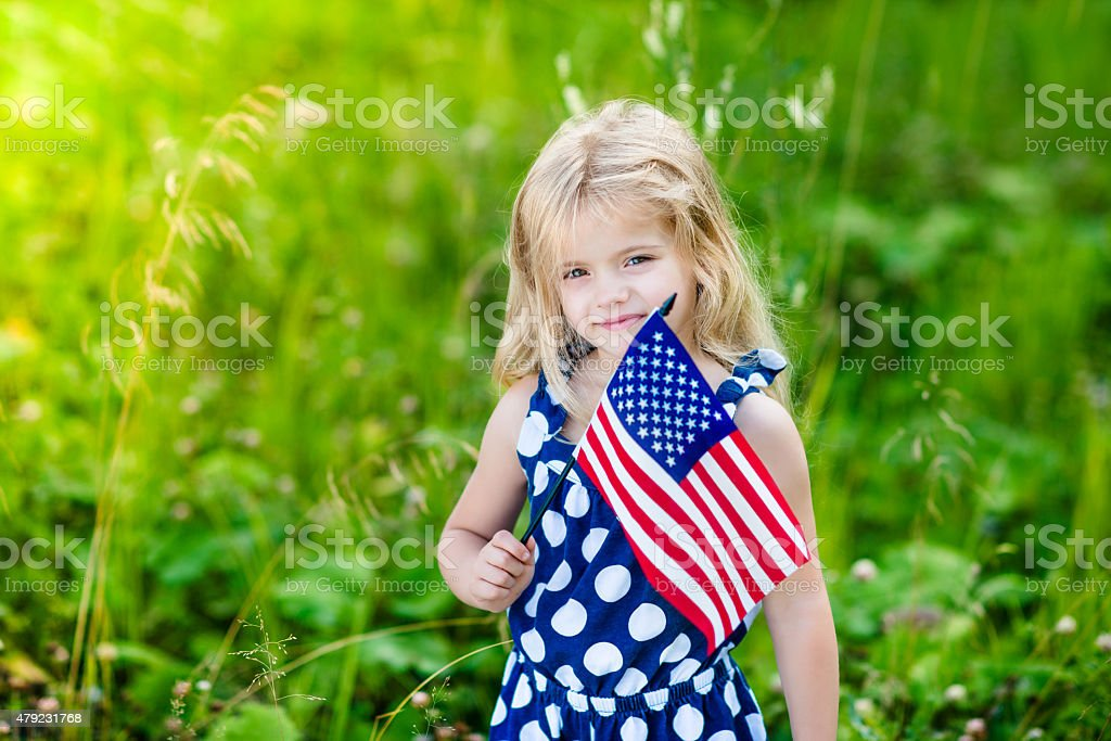 Blong smiling little girl with curly hair holding american flag stock photo