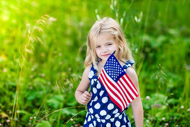 Blong lächelnden kleinen Mädchen mit lockigem Haar, die amerikanische Flagge – Foto