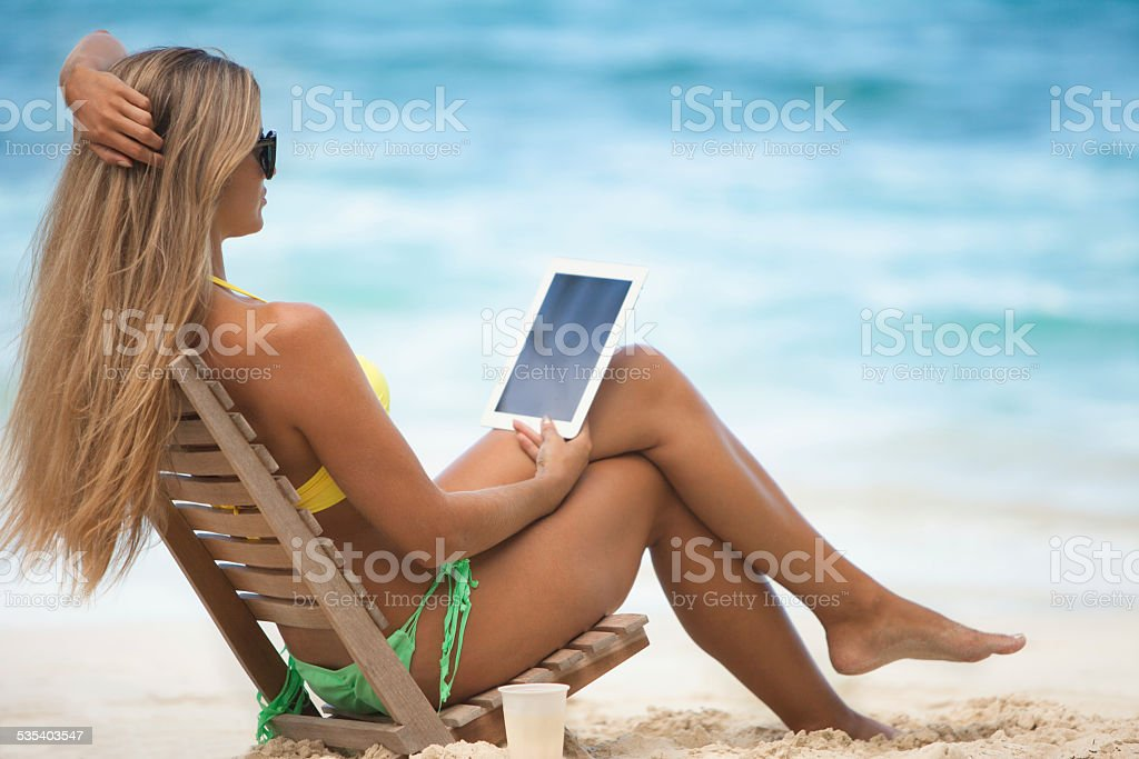 blong woman in a beach chair and using tablet computer stock photo