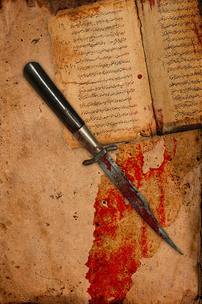 Blood Covered Knife on Ancient Antique Paper and Book stock photo