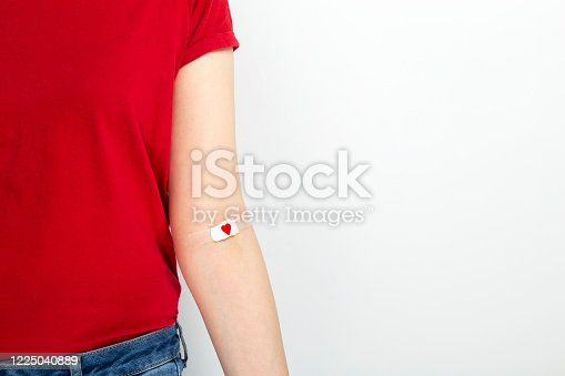 Blood donorship. Young girl in red T-shirt hand taped with patch with red heart after giving blood on gray background. Copy space