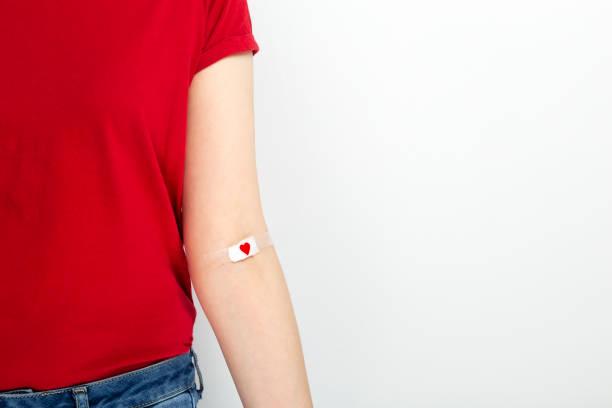 bloddonering. ung flicka i röd t-shirt hand tejpad med lapp med rött hjärta efter att ha gett blod på grå bakgrund. kopiera utrymme - ge bildbanksfoton och bilder