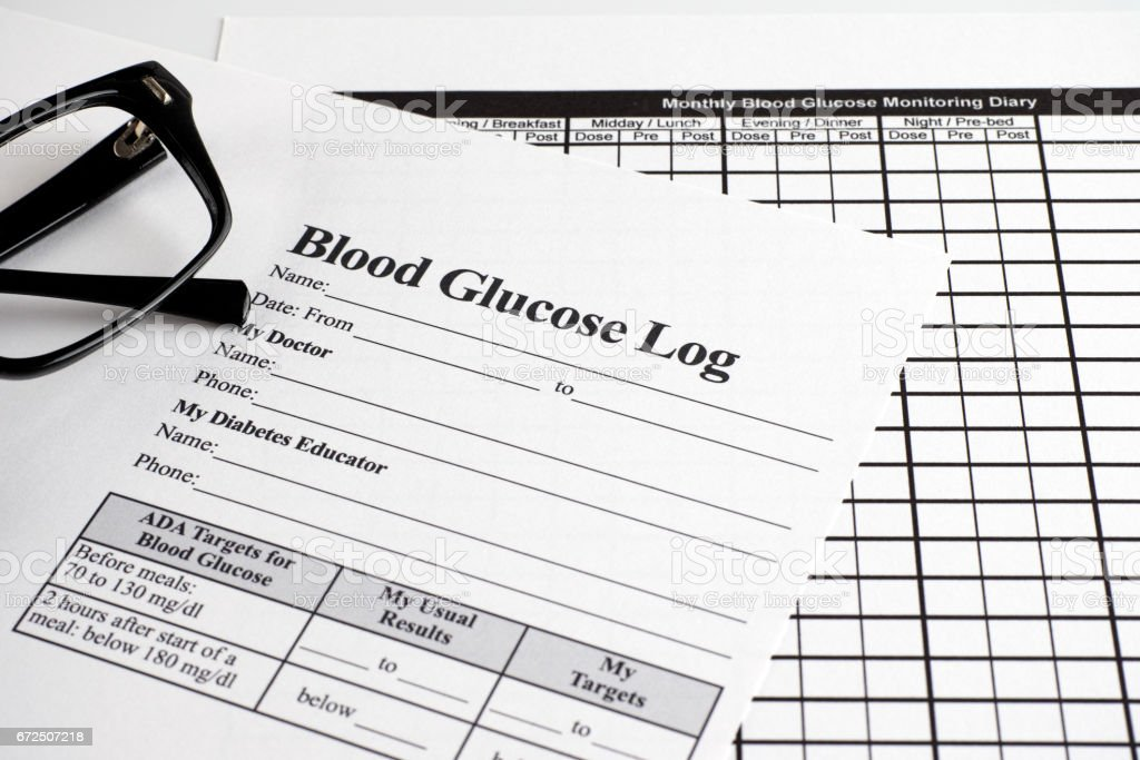 Blood Glucose Log and Monthly Blood Glucose Monitoring Diary forms with glasses stock photo