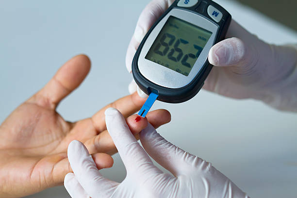 blood glucose meter on finger Hand of doctor and white glove show blood glucose meter, the blood sugar value is measured on a finger human pancreas stock pictures, royalty-free photos & images