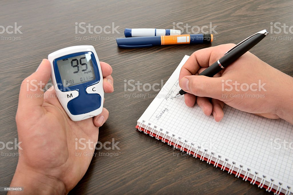 Blood glucose monitoring diary stock photo