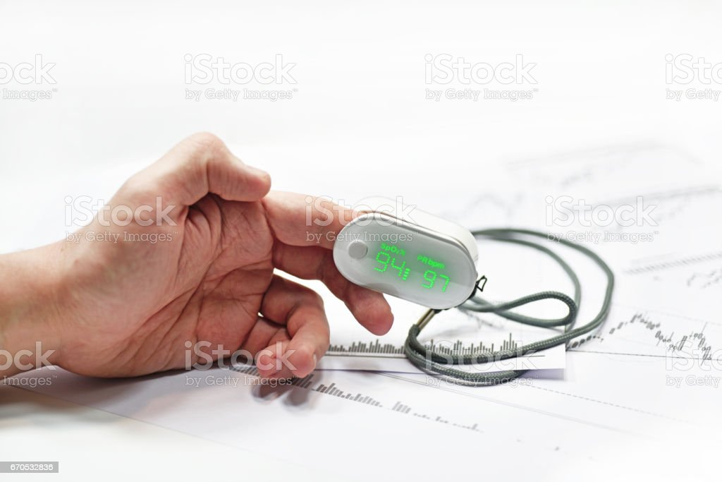 Blood oxygen meter on mans finger. stock photo