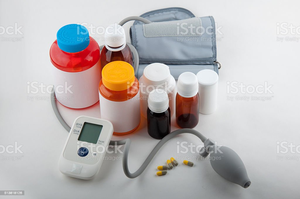 Blood preasure tonometer and bottles for tablets on white stock photo