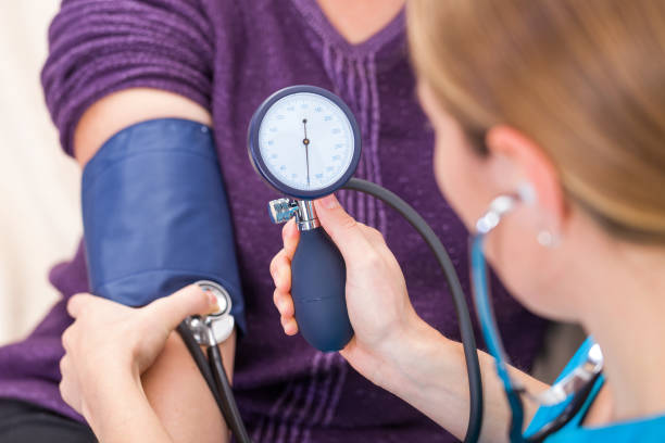 blood pressure measurement - assistant stock pictures, royalty-free photos & images