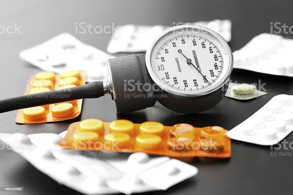 blood pressure meter and pills on the table royalty-free stock photo