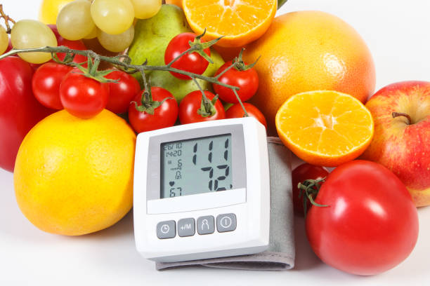 Blood pressure monitor and fresh ripe fruits with vegetables, healthy lifestyle and nutrition stock photo