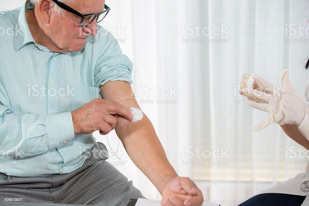 Blood sampling by an older man stock photo