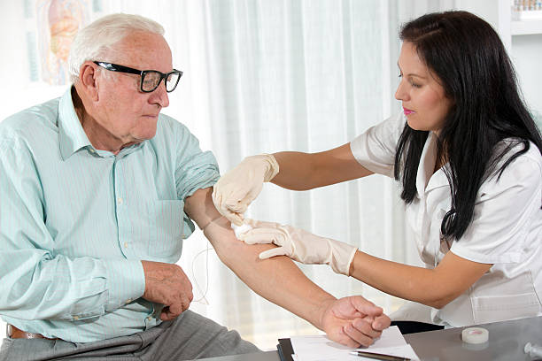 blood sampling by an older man - blood testing stock pictures, royalty-free photos & images