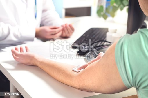 Blood test, sample or donation concept. Doctor with patient in hospital office, emergency room or laboratory. Person holding swab on arm after injection. Nurse holding needle.