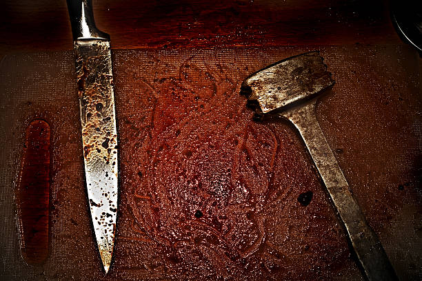 Bloodied metal hammer and knife stock photo